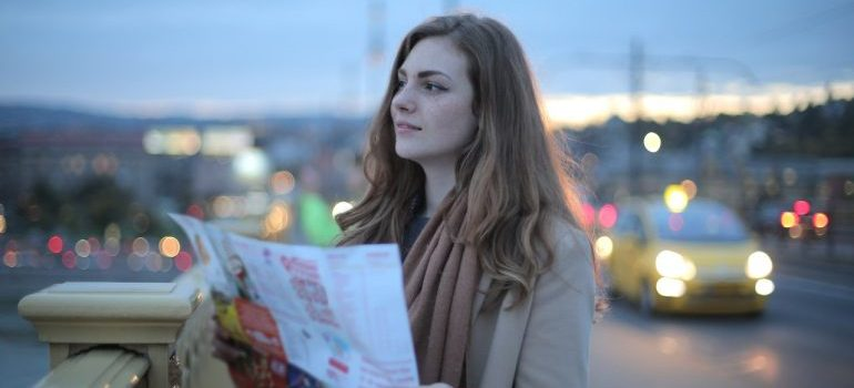 A girl holding newspaper and looking at the city because she is moving from NYC.