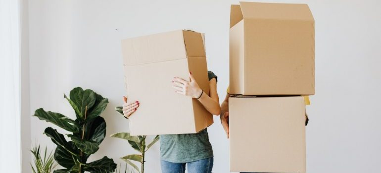 a couple holding moving boxes, representing moving from maine to florida