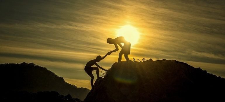 Two persons climbing a cliff at sunset.