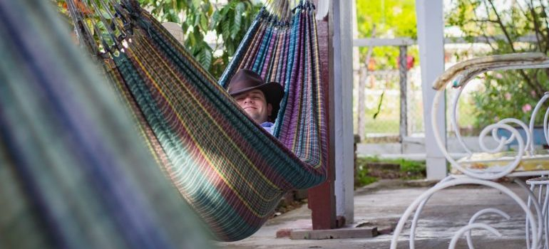 A man with fedora lounging in the hammock