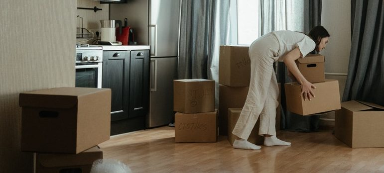Two people shuffling through moving boxes