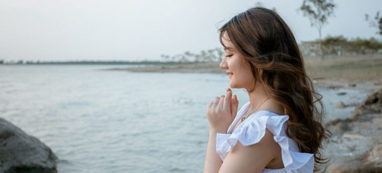 Woman with eyes closed sitting on the seashore