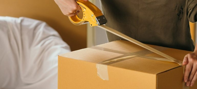A man taping up a cardboard box.