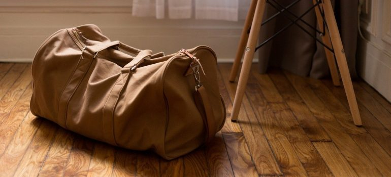 A brown travel bag on a wooden floor, representing things put into storage in Suffern NY.
