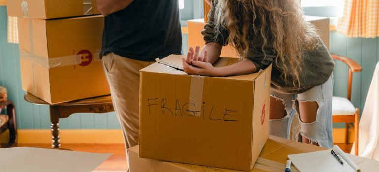 A woman leaning on a cardboard box.