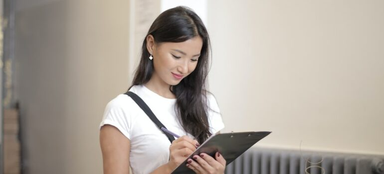 A woman writing something down on a tablet.