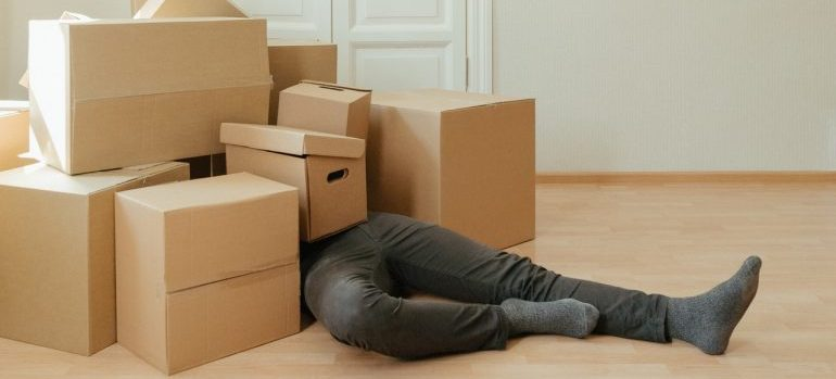 A man laying down surrounded by moving boxes.