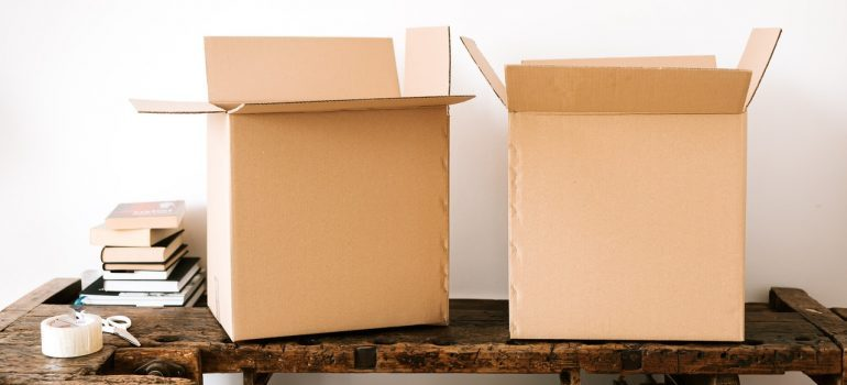 Two open cardboard boxes on a wooden surface.