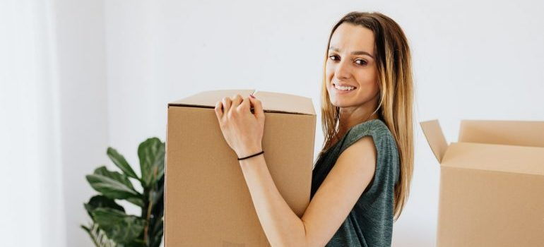 A woman carrying a moving box.