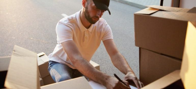 A man in a white shirt labeling cardboard boxes, representing movers Suffern NY.