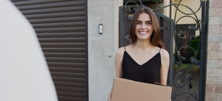 a woman standing in front of a garage door with a cardboard box.