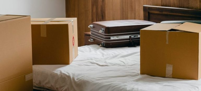 A suitcase next to cardboard boxes on a bed.