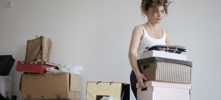 A woman carrying piles of boxes and papers next to other cardboard boxes.