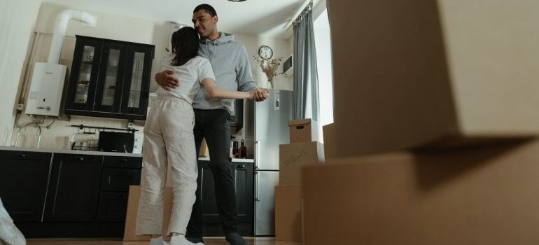 Couple dancing next to moving boxes after movers Orangeburg NY help them move
