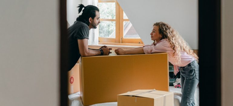 Two people looking at each other across a cardboard box.