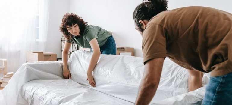 A man and a woman preparing a couch for the moving.