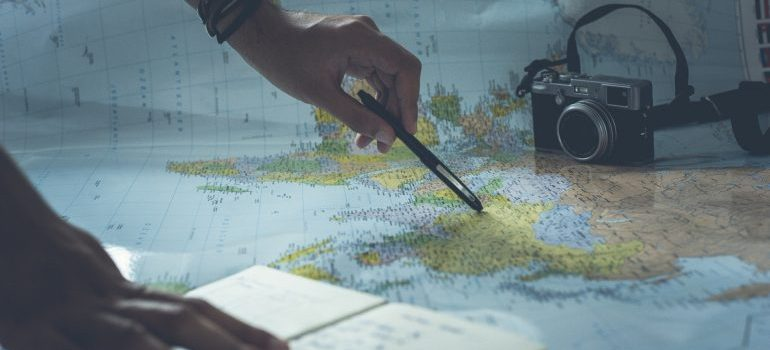 a person holding a pen over a map