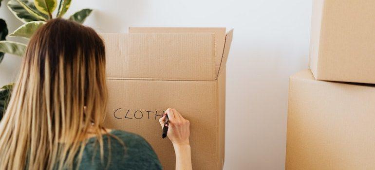woman writing on a box