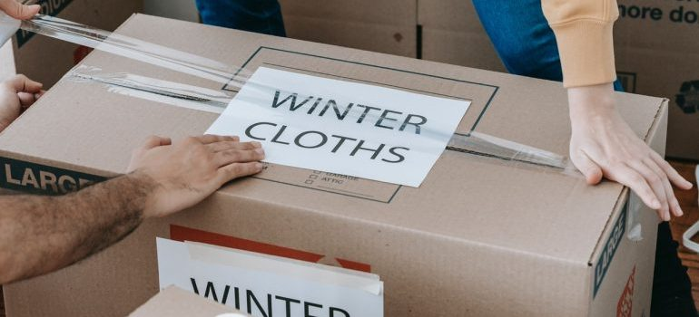 """box with """"winter clothes"""" label on it, prepare clothes for storage"""