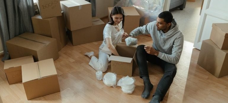 girl and a guy sitting on the floor surrounded with boxes packing