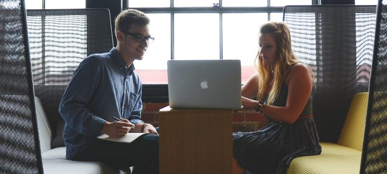 Two people looking at the laptop