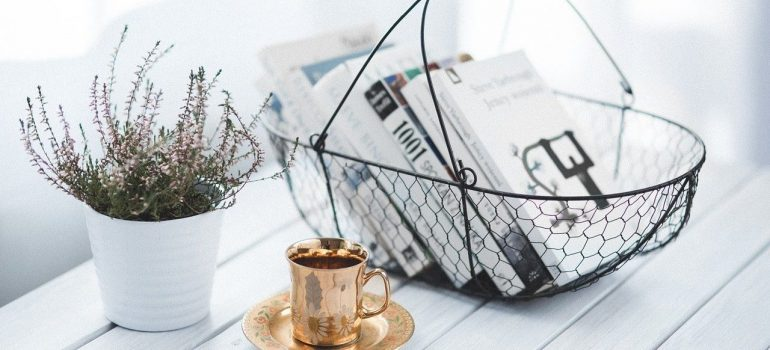 White wooden table, with a white pot and flowers, a metal coffee cup and a wire basket containing books.