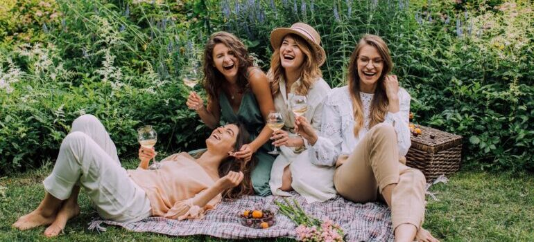 four women laughing and picnicking