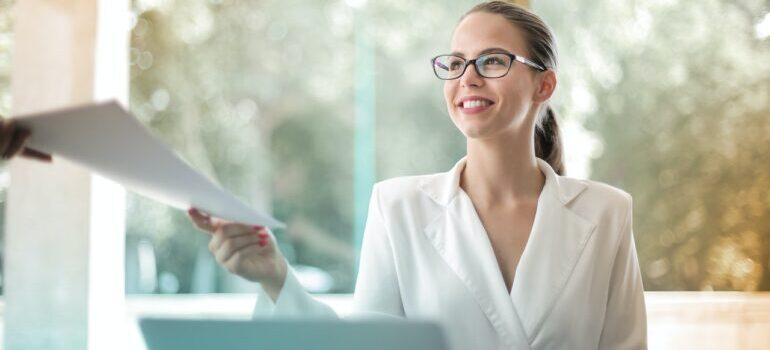 a woman smiling and doing her paperwork in the office