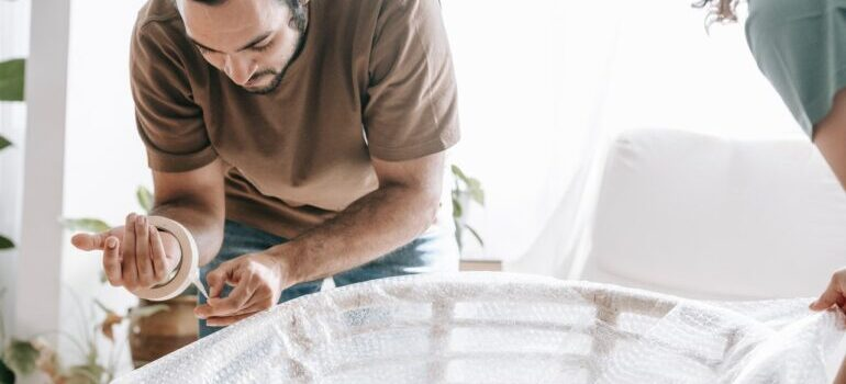pack fragile office items like this man wrapping a chair with a bubble wrap