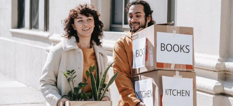 A couple carrying moving boxes