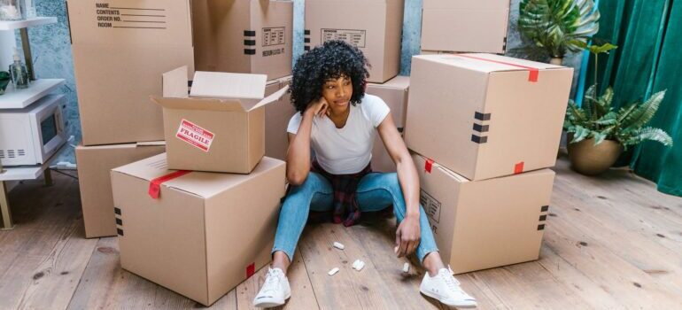 A girl sitting between moving boxes