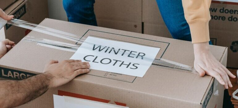 a woman and man taping and labeling a box with winter clothes